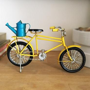 Διακοσμητικό κίτρινο ποδήλατο με μπλε ποτιστήρι.